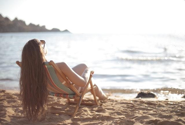 Une femme est sur un transat sur la plage